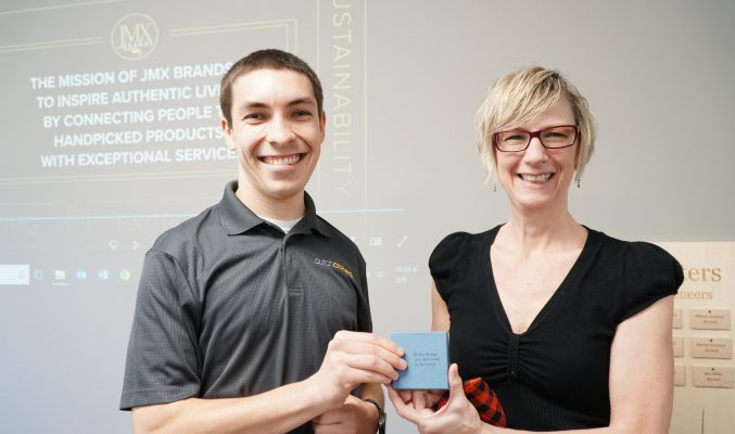 From Left to Right: Multimedia Producer and Graphic Designer Jake Smucker and Director of Marketing Debra Gingerich holding the JMX Brands Service Award